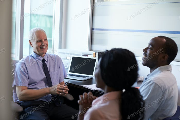 Doctor In Consultation With Couple In Office