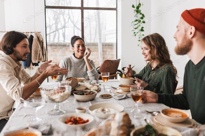 Young colleagues joyfully spending time together on lunch in cozy cafe