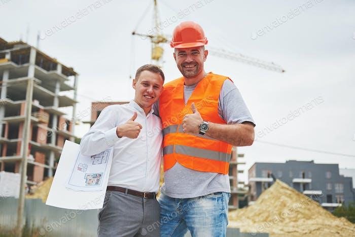 glückliche Architekten mit Bauplan auf Baustelle