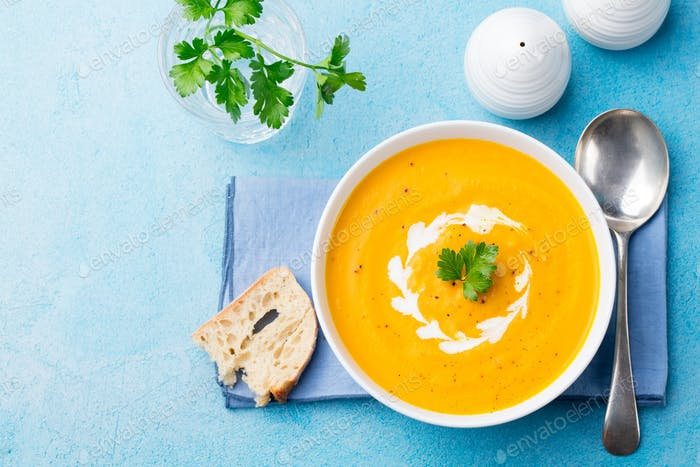 Pumpkin and Carrot Soup with Cream and Parsley on Blue Stone Background. Top View. Copy Space.