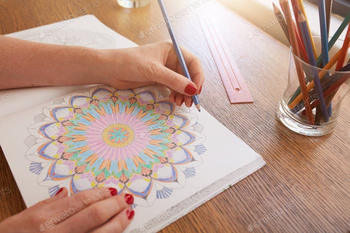 Woman hands drawing in adult colouring book