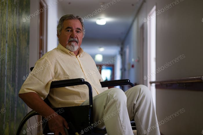 Portrait of senior man sitting on wheelchair in corridor