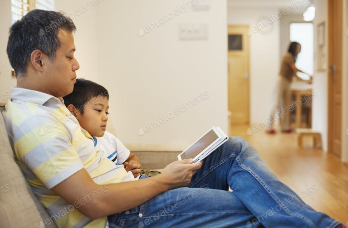 Family home. A man and his son sitting reading a book.