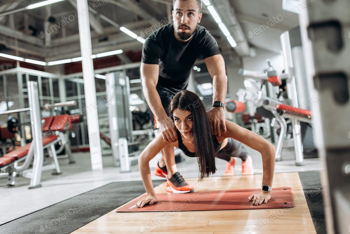 Beautiful athletic girl dressed in black sports top and tights is doing plank and the coach corrects