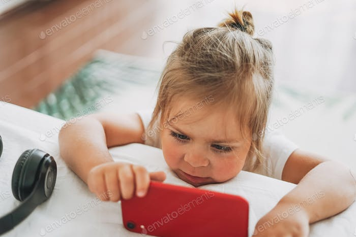 Cute toddler girl with fair hair watching mobile on bed