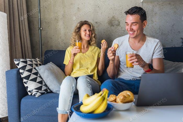junger Mann und verliebte Frau sitzen zu Hause und arbeiten online