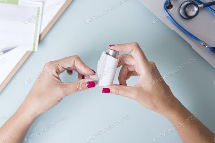 Female hands hold an aerosol inhaler
