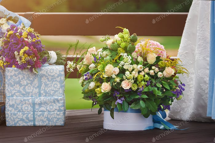 Beautiful bouquet next to wedding gifts outdoors