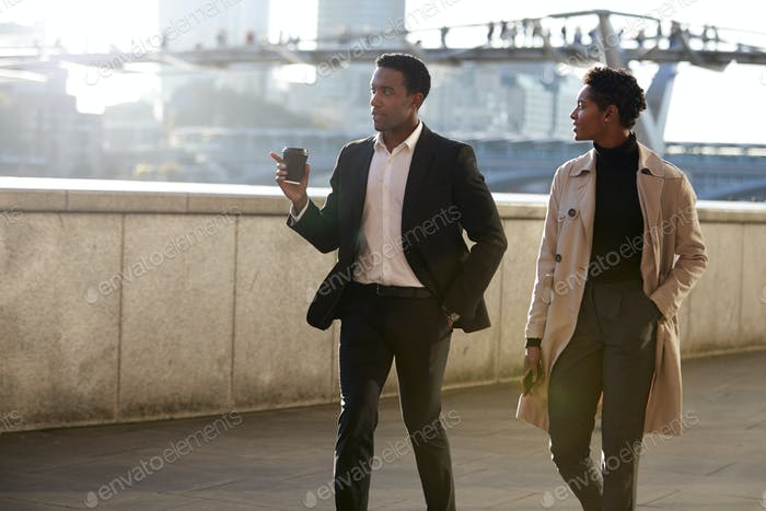 Two business colleagues walking by the Thames riverside in the city of London talking, man gesturing