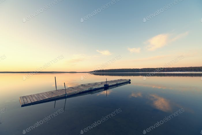 A wooden dock floating on flat calm waters of a lake at sunset.