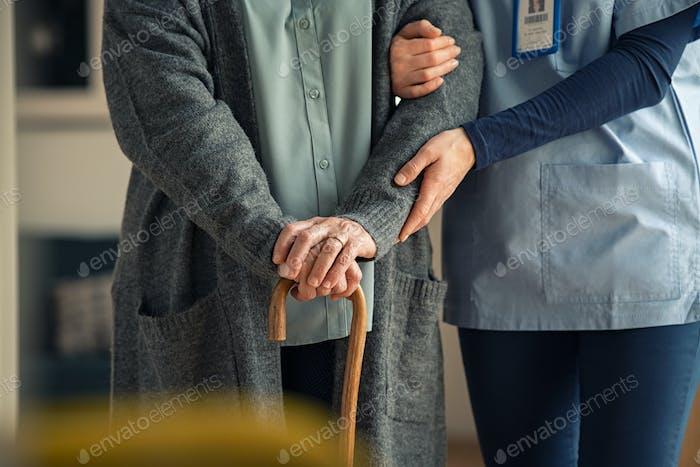 Nurse assisting senior with walking cane