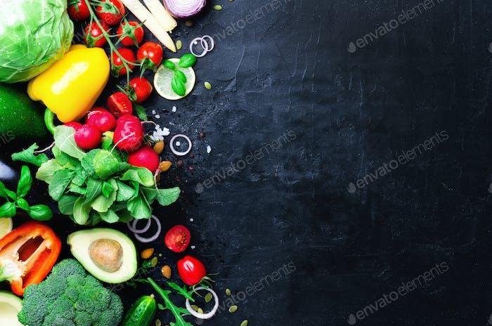 Set von frischem Gemüse auf schwarzem Hintergrund. Aromatische Kräuter, Zwiebel, Avocado, Brokkoli, Pfefferglocke