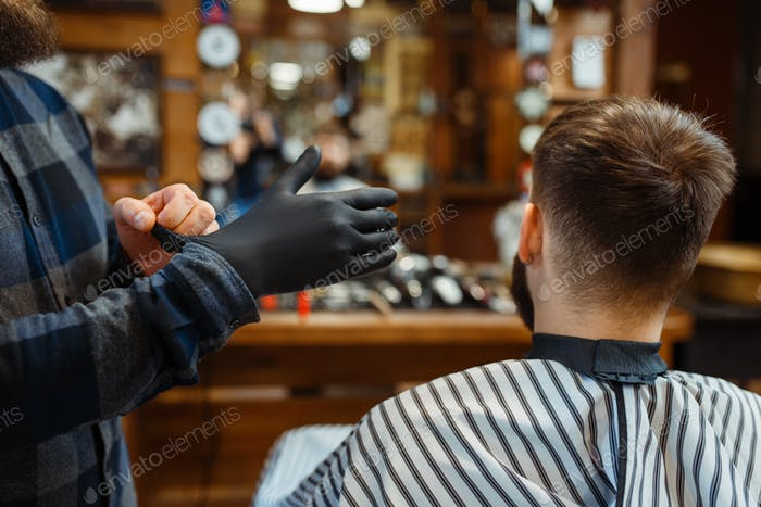 Barber puts on gloves, customer sitting in chair