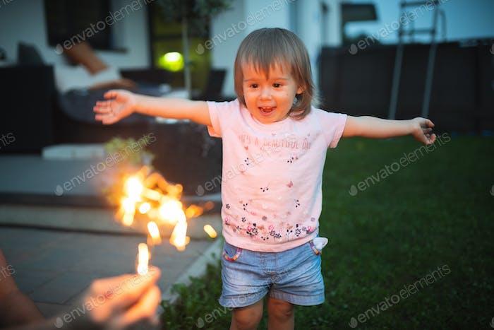 Baby glücklich sehendes glitzerndes glitzerndes und lächeln glücklich mit breiten Händen.