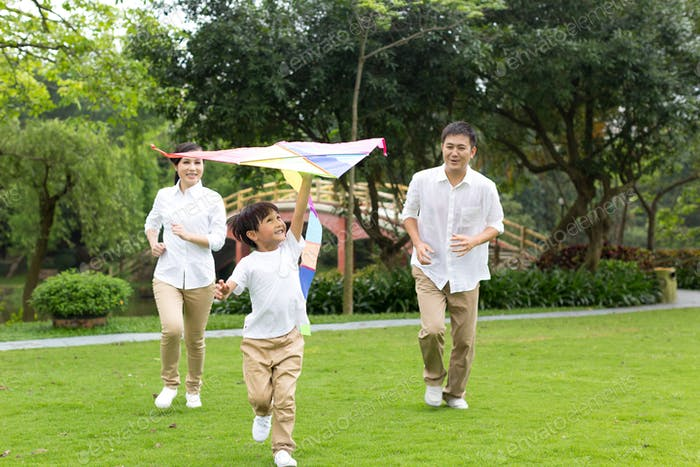 Happy family  flying kite in the park