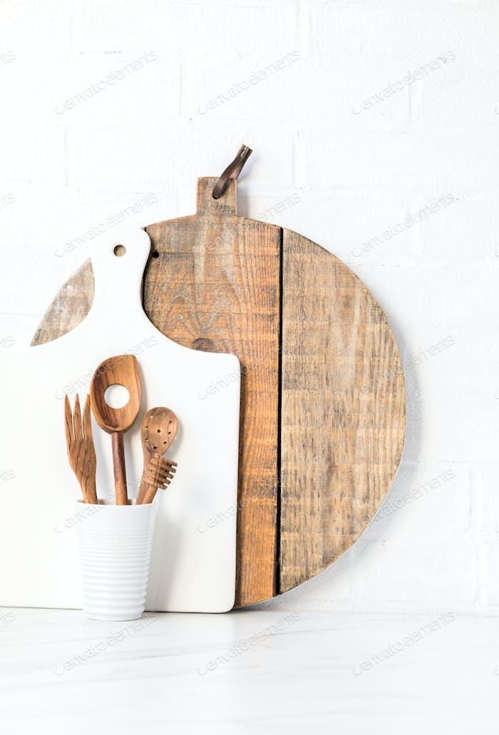 Küchenutensilien auf einem Hintergrund einer weißen Ziegelmauer. Konzept des Dekors der Küche.