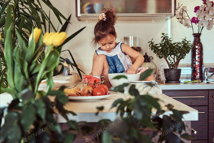 Sweet little cute girl learns to cook a meal in the kitchen.