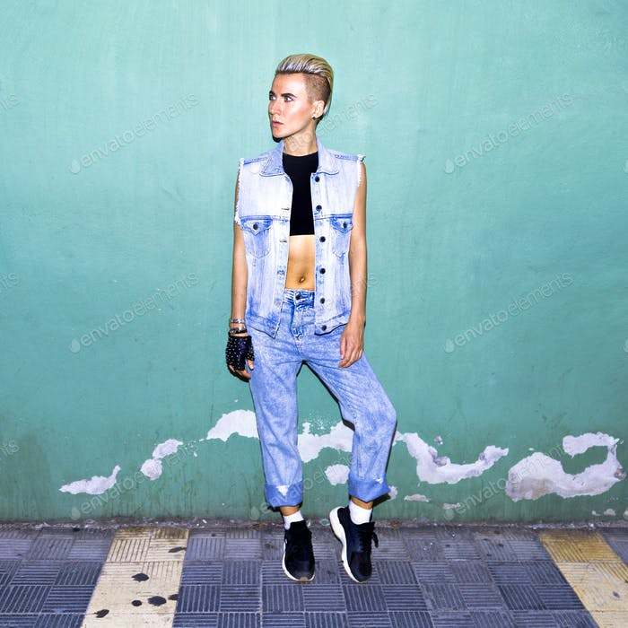 Model in a stylish jeans outfit near a blue wall