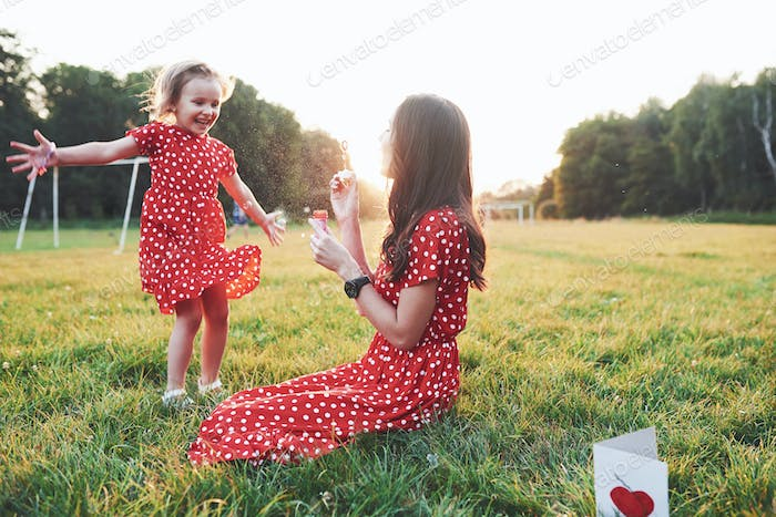 Give me more. Girl with her daughter having fun with bubbles outside sitting on the grass
