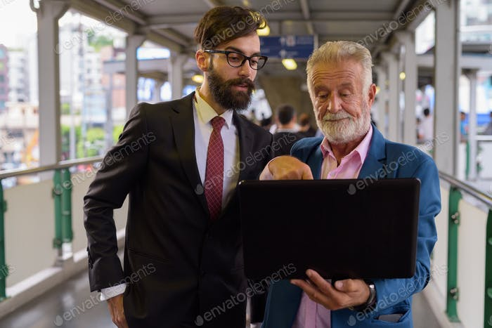 Two multi ethnic bearded businessmen together around the city
