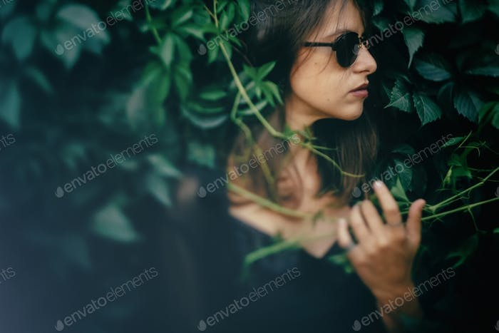 Fashionable woman holding branch at bush in evening