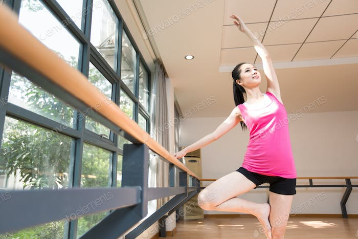 Young woman stretching in the gym