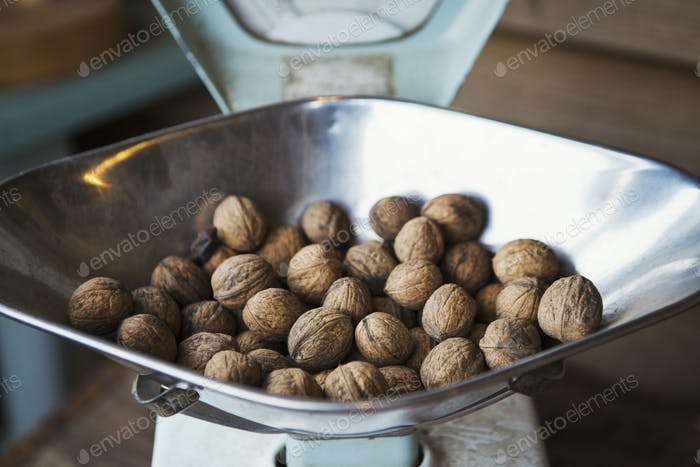 Close up of walnuts on metal weighing scales.