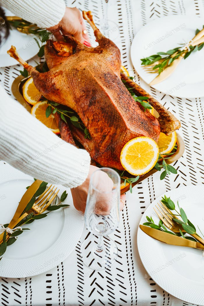 Woman sets a golden tray with whole roasted goose