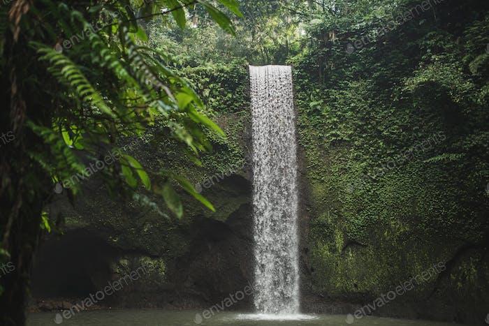 Pequeña cascada secreta Tibumana en Bali, Indonesia. Lugar de referencia turístico popular en la selva verde exuberante