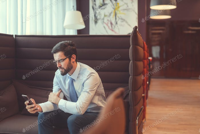 Young businessman with a phone indoors