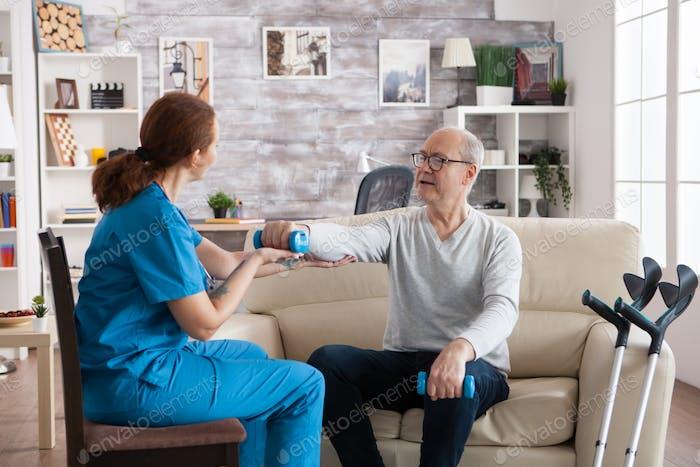 Молодая медсестра делает физиотерапевтическое лечение в доме престарелых