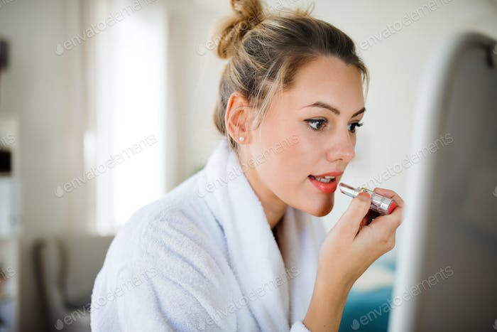 Young woman indoors at home in the morning, putting on lipstick.