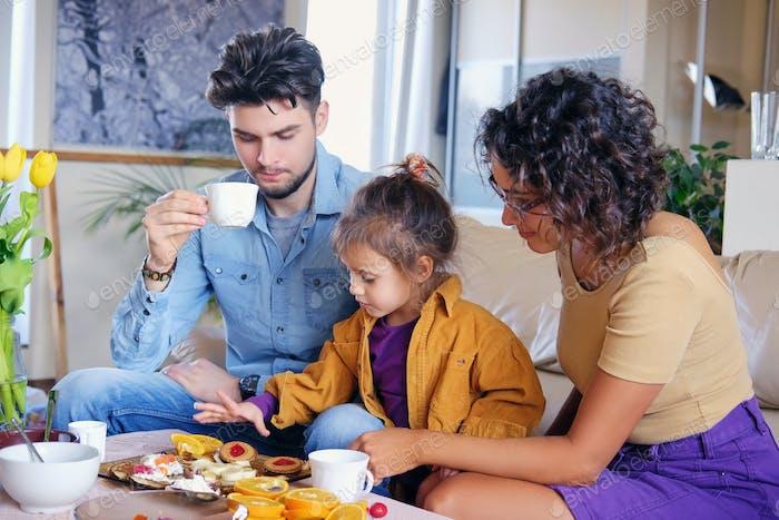 Счастливая семья за столом в гостиной.