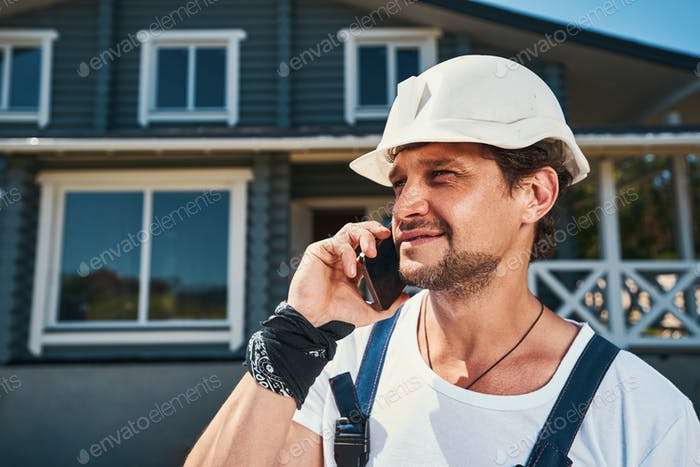 Builder having a phone call on hot summer day
