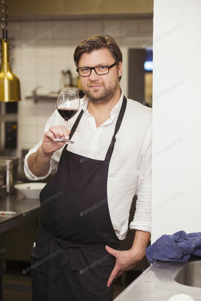 Porträt des selbstbewussten Küchenchefs mit rotem Weinglas, während er in der kommerziell Küche steht