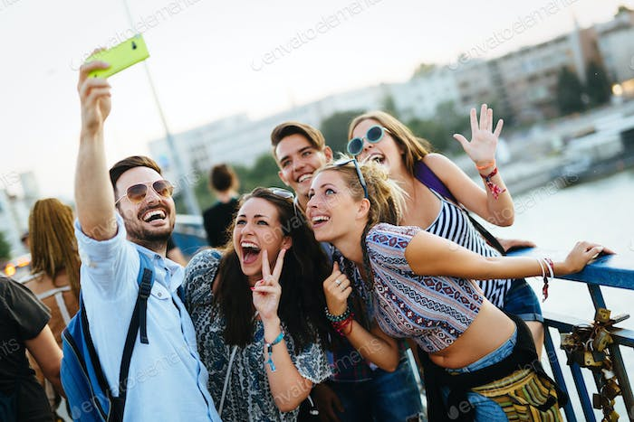 Happy young friends taking selfie on street