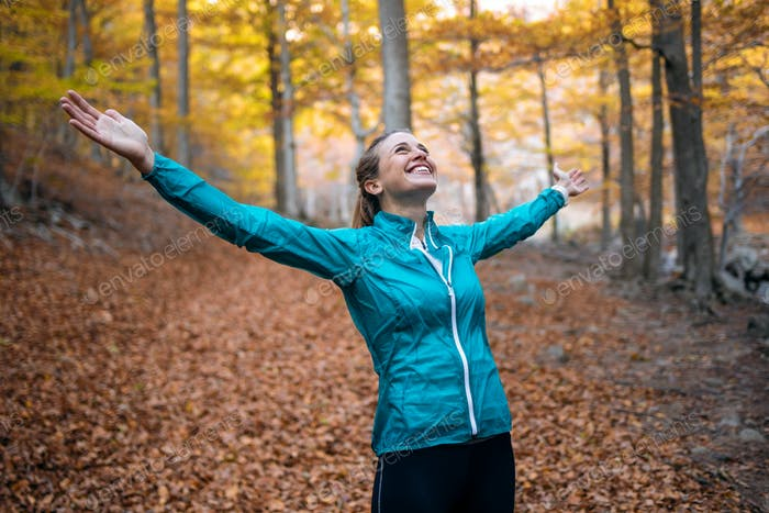 Sporty young woman with raised up hands enjoying the nature in the park in the autumn morning.