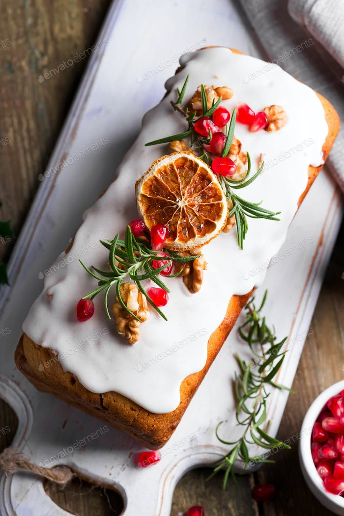 Fruit cake dusted with icing, nuts, kernels pomegranate and dry orange close-up. Christmas and