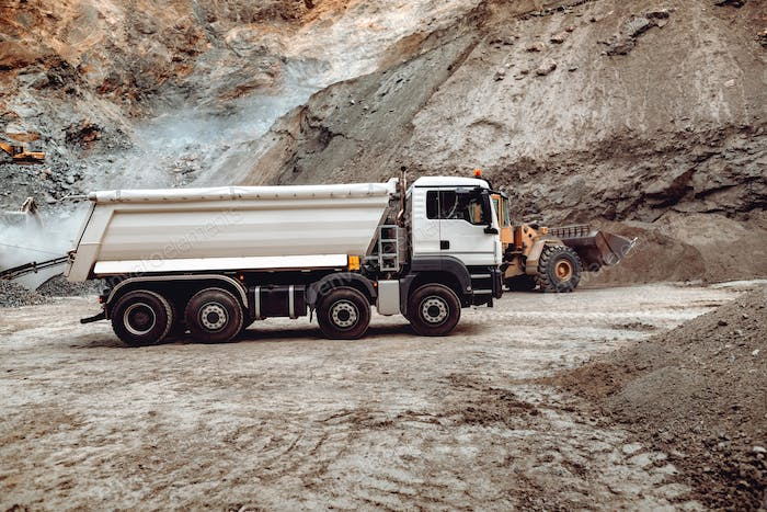 Industrial dumper trucks working on highway construction site, loading and unloading