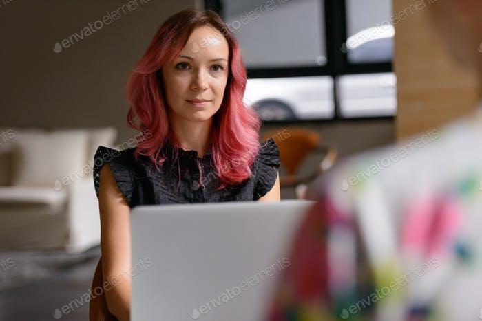 Beautiful businesswoman using laptop and talking with man indoors
