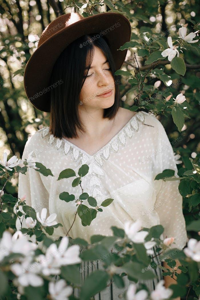 Ruhiges Porträt von schönen Hipster Mädchen stehend in weißen Blüten im Frühling