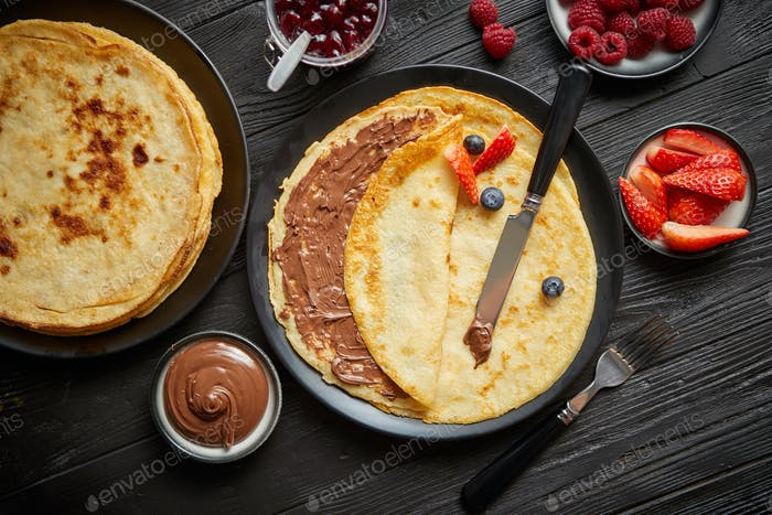 Delicious chocolate homemade pancakes on black ceramic plate