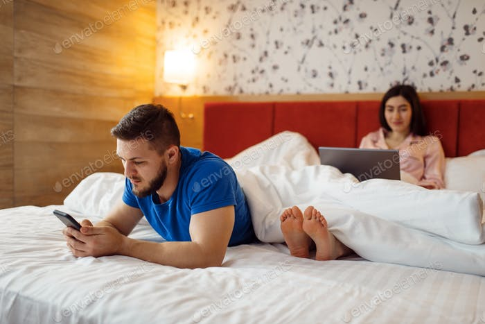 Couple uses their gadgets in bed, carefree weekend