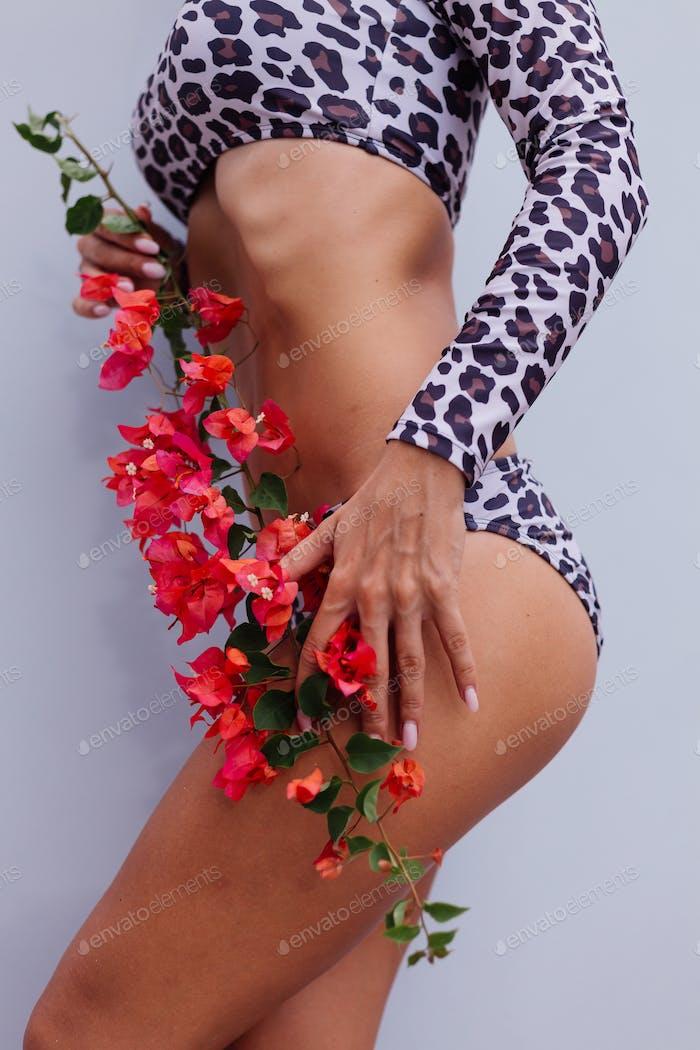 Fitte Frau im Leoparden-Bikini mit Blumen
