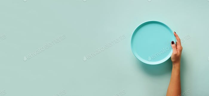 Female hand holding empty blue plate on pastel background with copy space. Healthy eating, diet