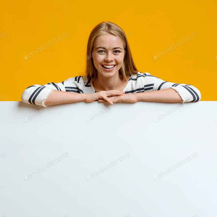 Smiling teenage girl leaning on blank white board