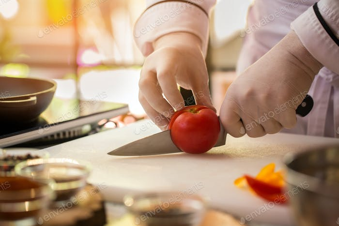Hand with knife cuts tomato