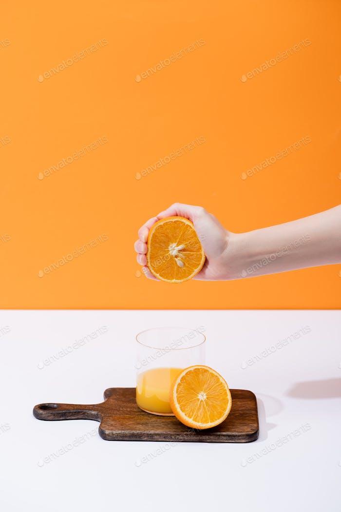 vista recortada de mujer exprimir jugo de naranja fresco