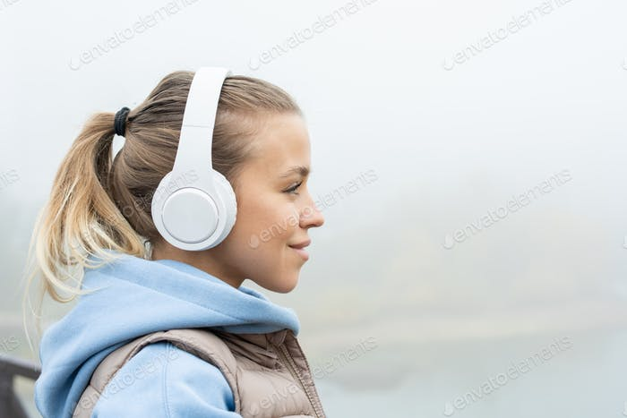 Side view of young contemporary sportswoman in headphones and activewear