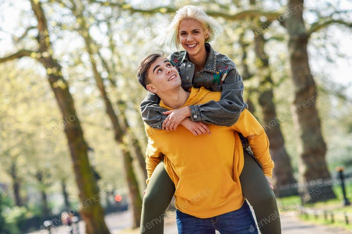 Funny couple in a urban park. Boyfriend carrying his girlfriend on piggyback.